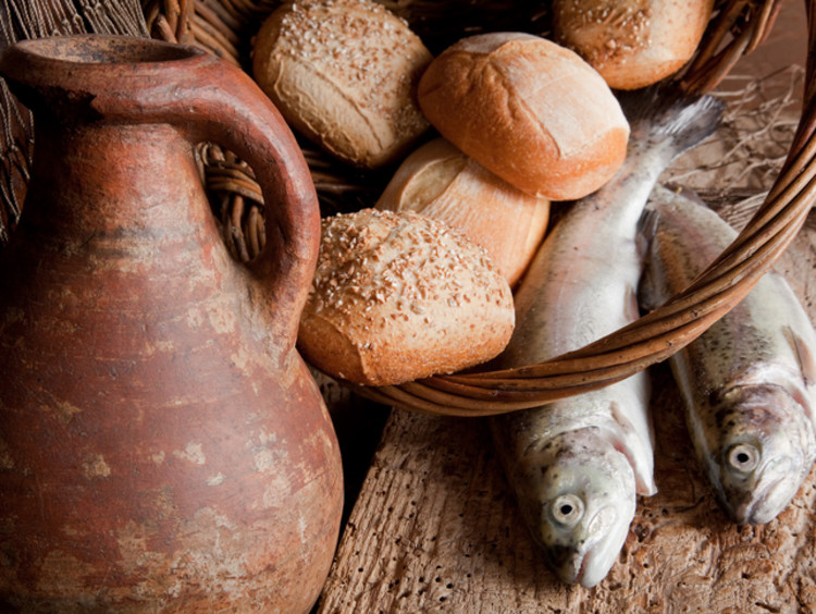 Loaves of bread and fish with old clay pitcher as a model for one of the miracles of Jesus