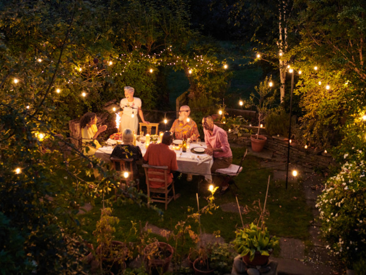 Friends having dinner together outdoors with clear lights in the trees