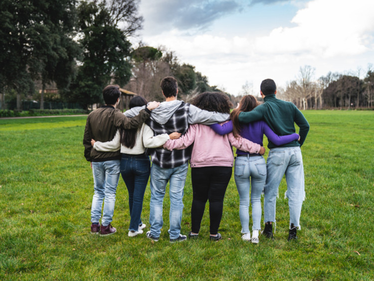Godly friends supporting each other with interlinked arms on a grassy field