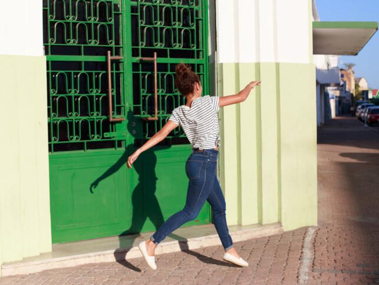 Woman joyfully skips along the sidewalk