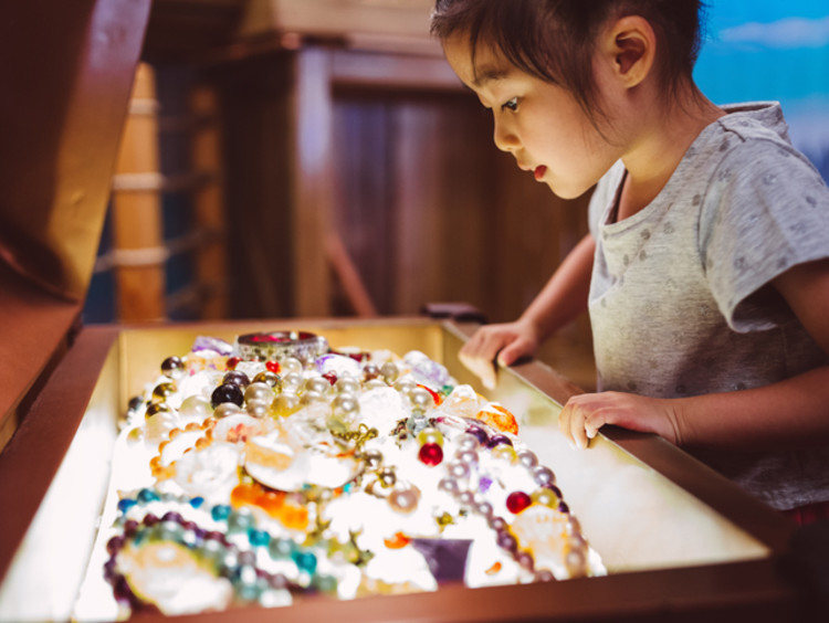 Little girl looking at pearls and other jewelry treasure in a chest