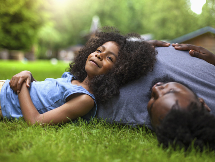Little girl looking peaceful laying her head on her dad on the lawn