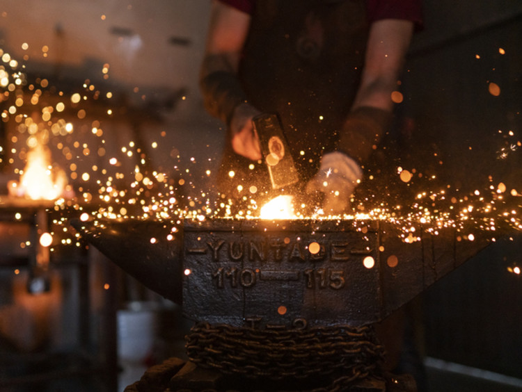 Man using his God given talents forging in his workshop