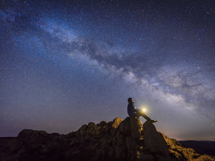Man sitting on rocks looking up at the stars with beautiful starlit sky above him