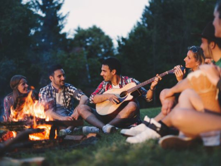 Friends gather and sing around a camp fire