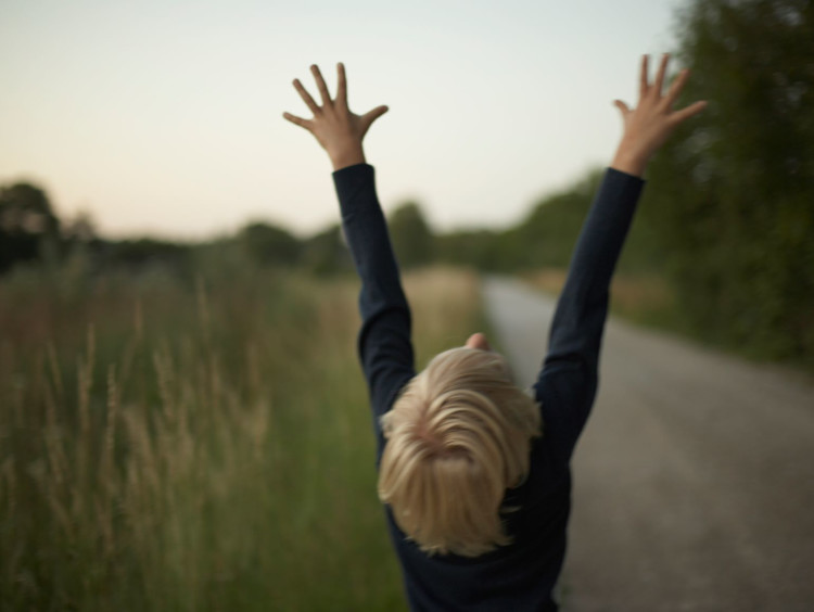 Young man throws his hands towards the Heavens