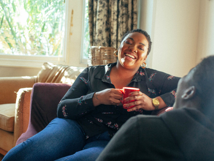 African-American woman having a conversation about faith with friend in a living room