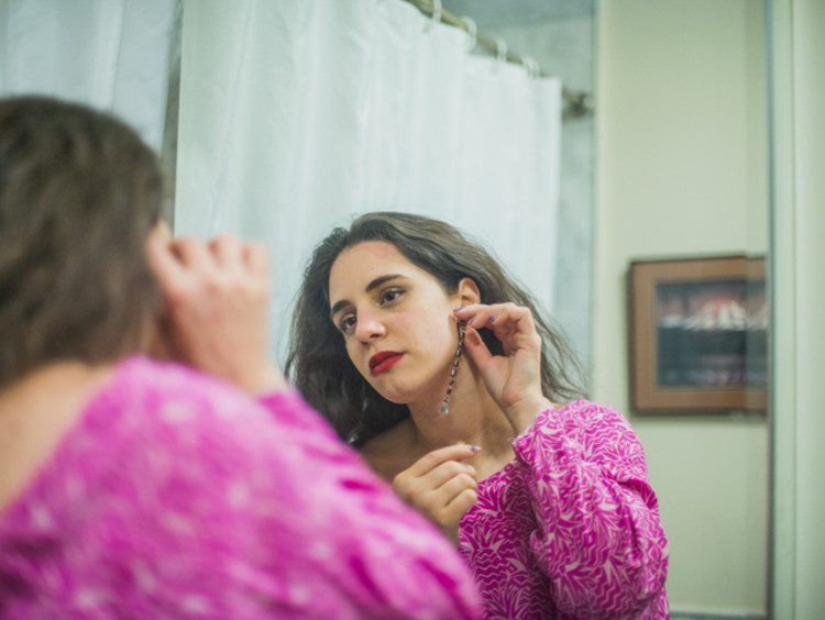 Caucasian brunette woman in pink dress putting earring on while looking in a mirror