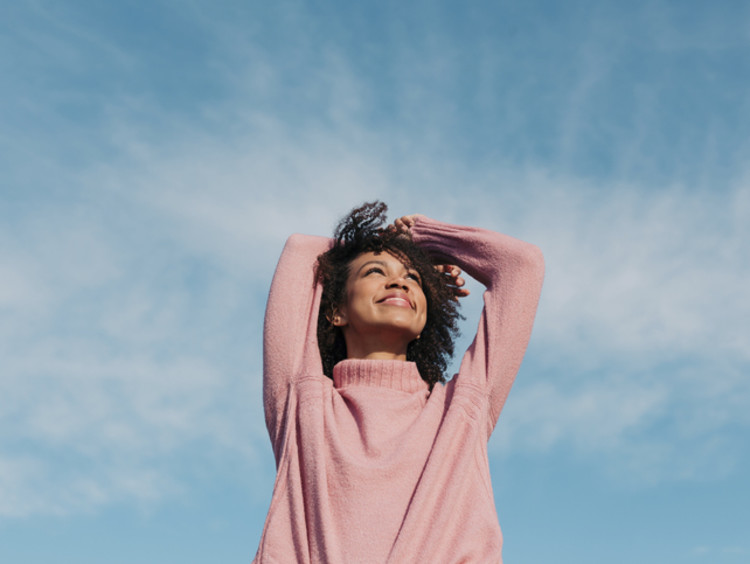 Woman smiles and looks up at the blue sky