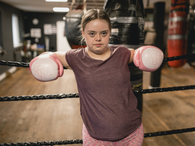 Young female boxer against the ropes fighting the good fight of faith