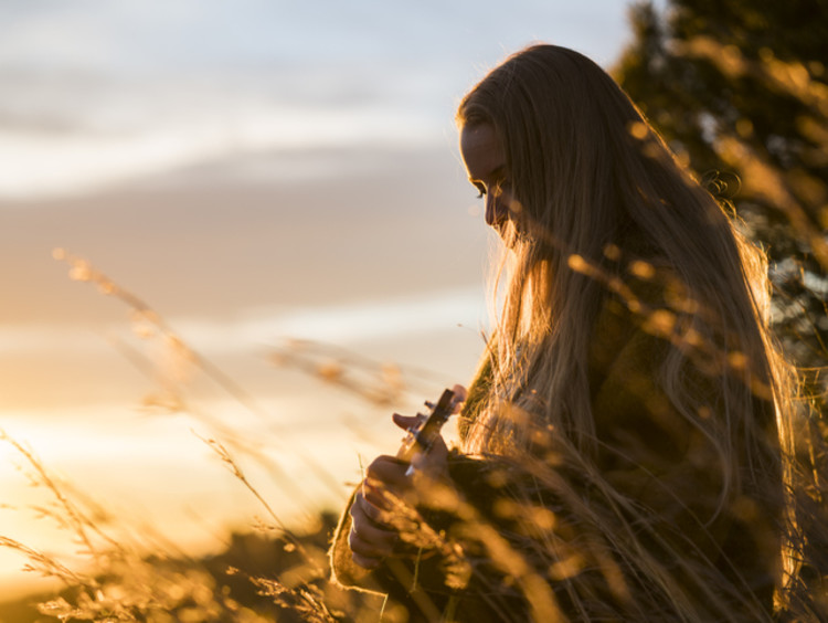 Young woman playing ukulele and worshipping in the early morning sunlight