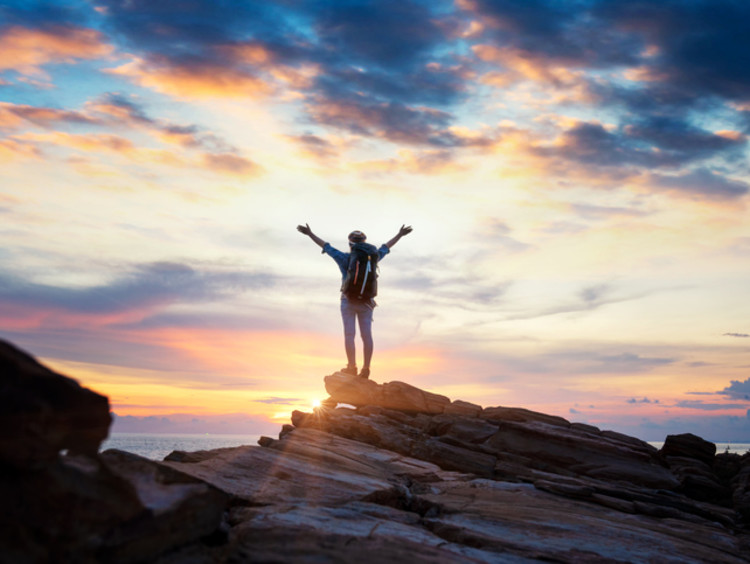 Person stands triumphantly on top of a mountain with sunset in horizon