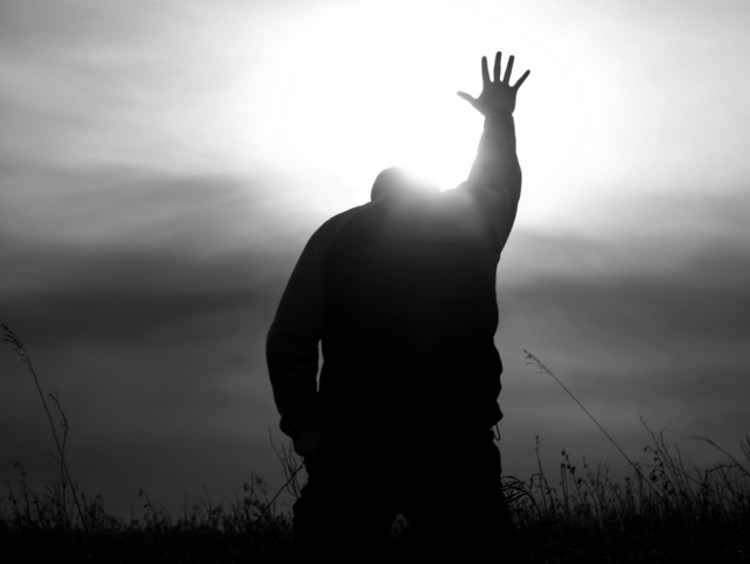 Black and white image of a man on his knees with one arm and hand raised up towards the sun