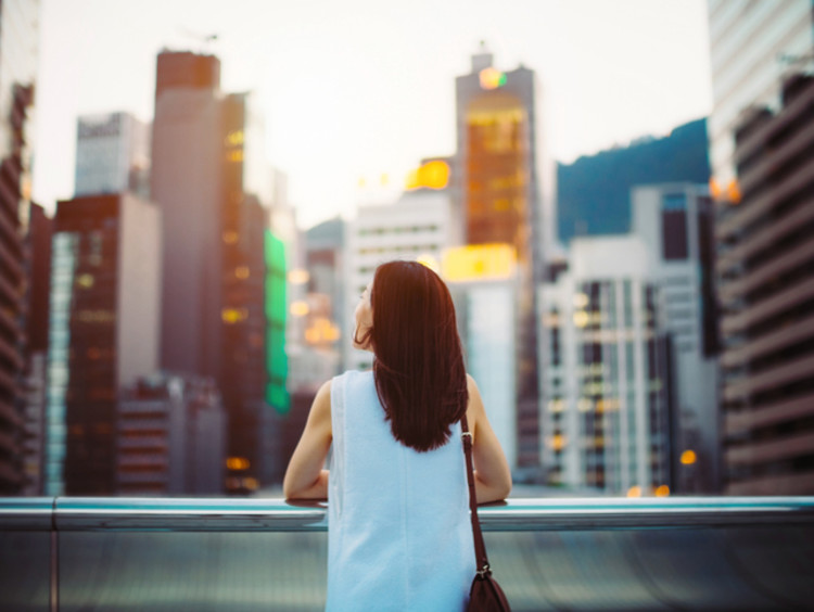 Deep thinking woman gazes out yonder at city skyscrapers