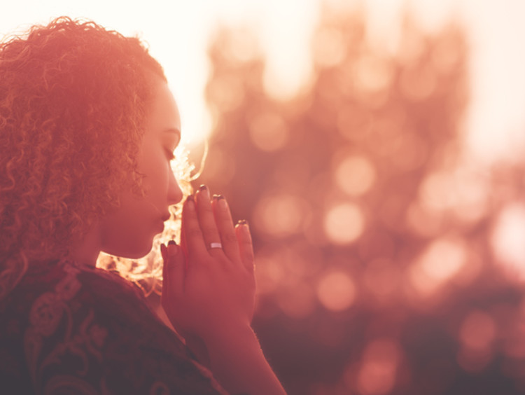 Woman praying outdoors with hands clasped as the sun sets
