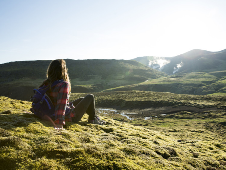 Woman sits on a grassy hill overlooking other grassy hills
