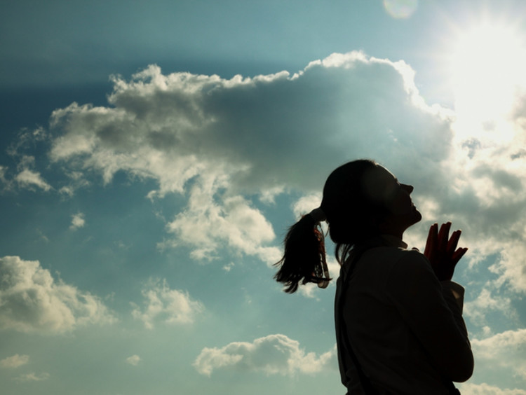 Woman smiles looking up to the sun with clouds in the sky behind her