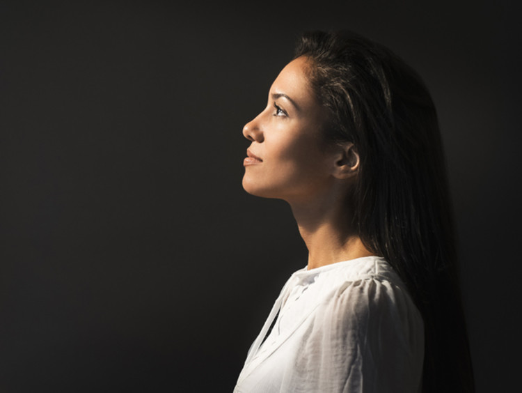 Young woman looks at the light to left with black background