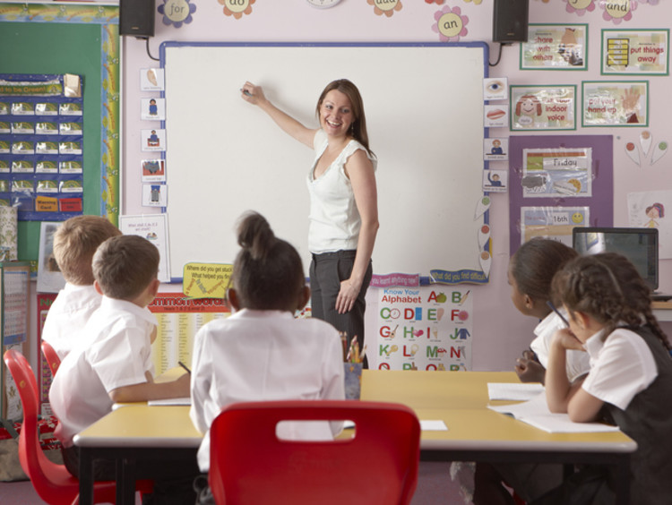 young students learning in classroom from female teacher writing on board