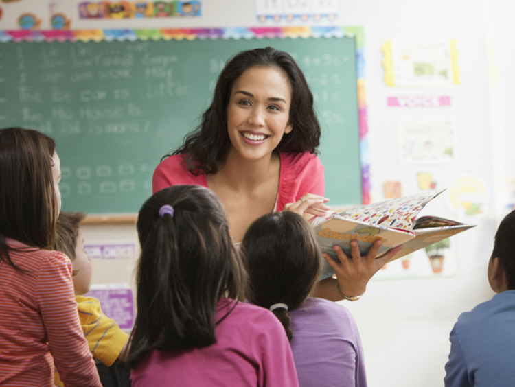 female teacher reading to young students