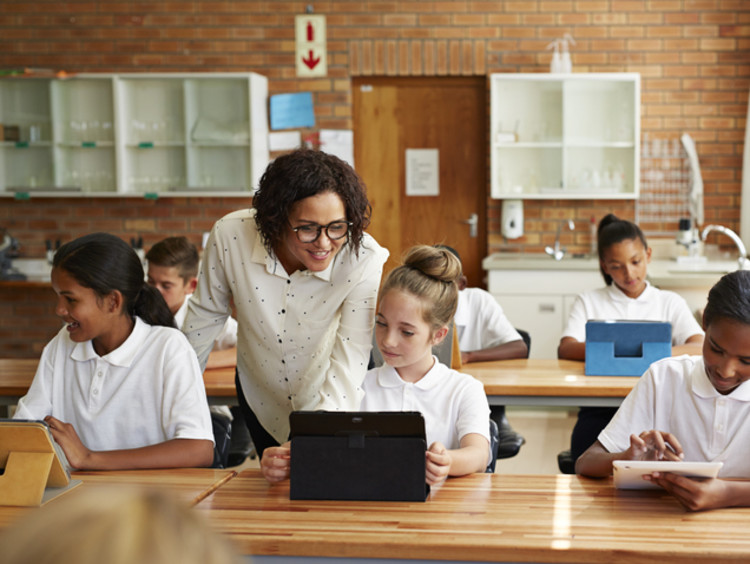 female teacher teaching young students in classroom learning environment