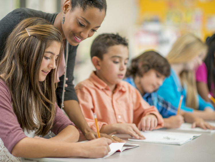 middle school teacher working with group of students