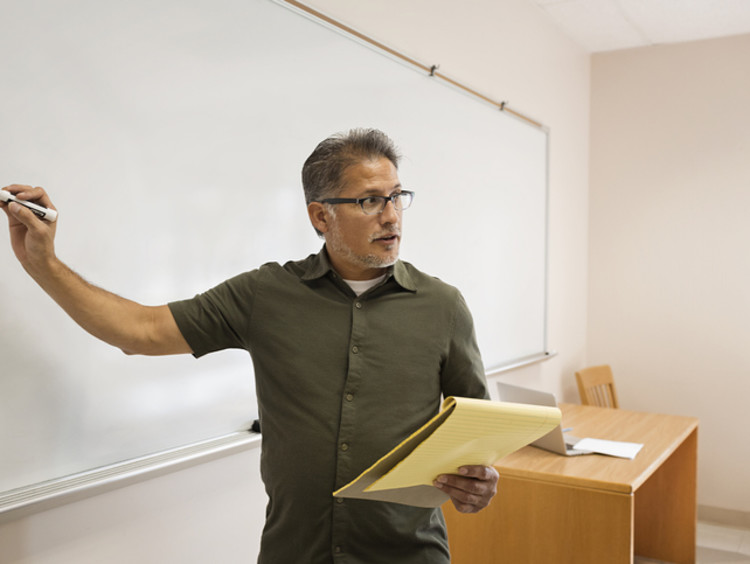 Male teacher writing on whiteboard to teach students how to learn to read