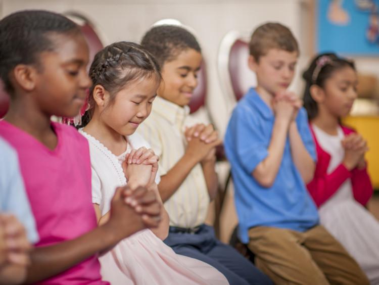 kids praying in school classroom