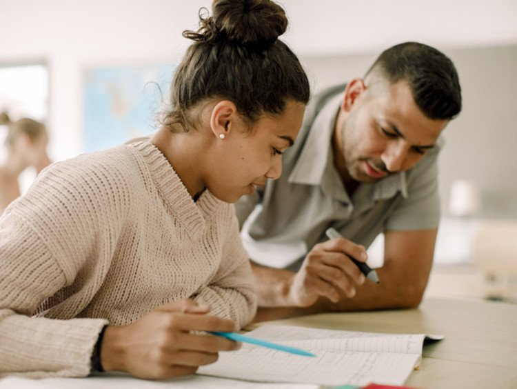 female student and male teacher reading together in classroom