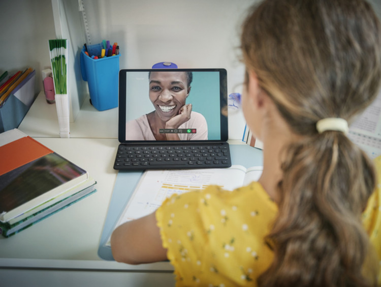 African-American female teacher laughs on young female student's laptop screen