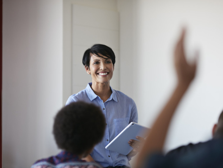 female teacher smiling in class to create happy learning environment