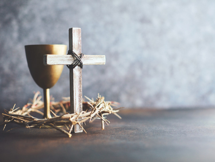 A cross sits with a wine glass and crown