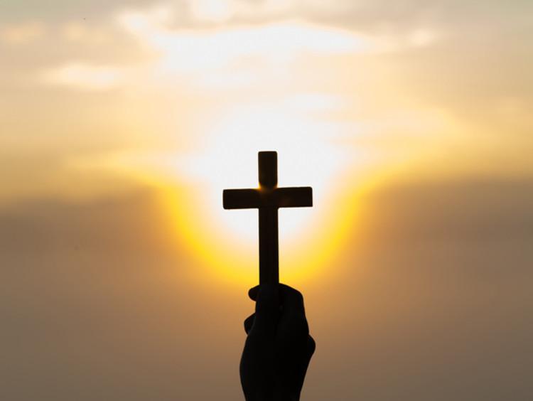 Man holding cross in hand against sunset sky
