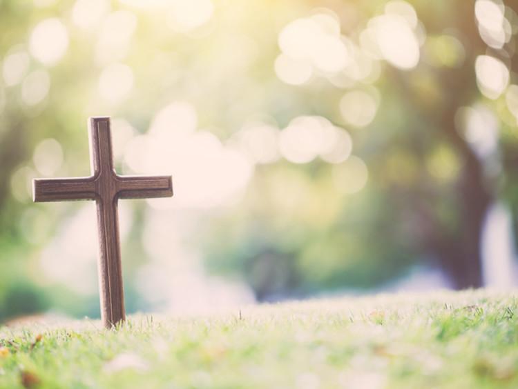 A cross stands alone in an empty grass field