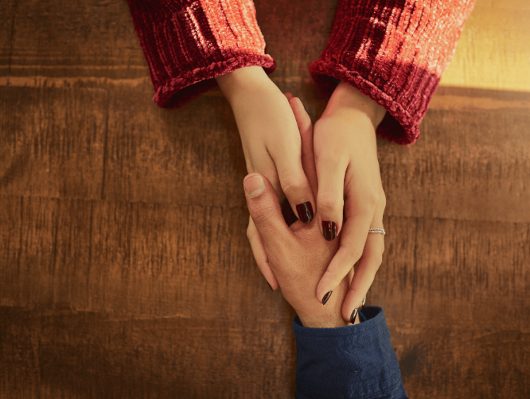Woman hands enclasps a male hand