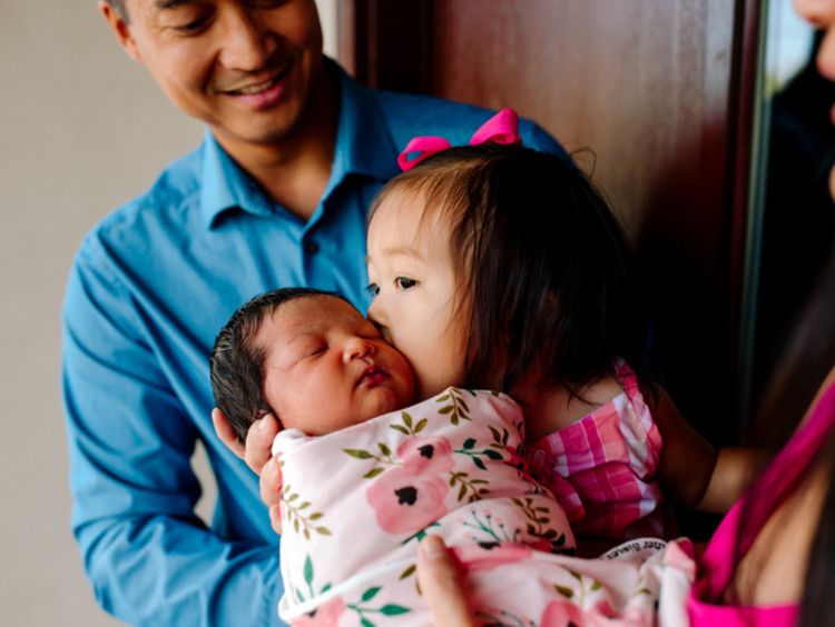 Little Asian girl kissing baby sister on the cheek while man in blue shirt watches