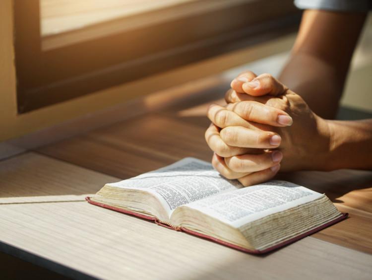 Praying hands rest on an open bible