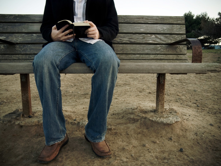 guy sitting on bench with open Bible