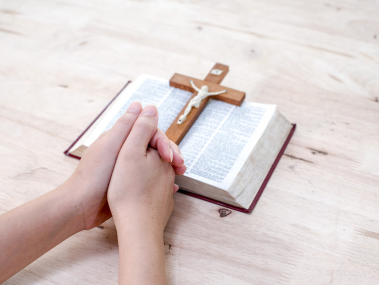 Praying hands rest at the foot of an open Bible