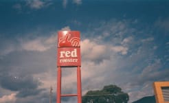 Red Rooster fast food sign against sky