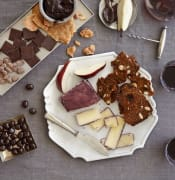 chocolate covered almonds, peanut brittle sliced pear cheese knife corkscrew wine bread with almonds raisins