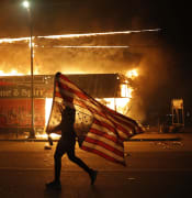 A protester carries a U.S. flag upside down, a sign of distress, next to a burning building Thursday, May 28, 2020, in Minneapolis. Protests over the death of George Floyd, a black man who died in police custody Monday, broke out in Minneapolis for a third straight night. (AP Photo/Julio Cortez)