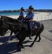 Police on horses enforce social distancing regulations to slow the spread of coronavirus disease (COVID-19) at Bondi Beach in Sydney, Saturday, April 4, 2020. (AAP Image/Steven Saphore) NO ARCHIVING