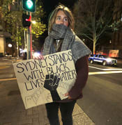 A protester from St. Louis, U.S., who gave her name as Merinda, carries a handmade sign as demonstrators gather in Sydney, Tuesday, June 2, 2020, to support the cause of U.S. protests over the death of George Floyd and urged their own governments to address racism and police violence. Floyd died last week after he was pinned to the pavement by a white police officer who put his knee on the handcuffed black man
