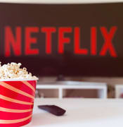 Istanbul, Turkey - July 03, 2020: Table with popcorn bottle and Netflix logo on TV. Netflix is a global provider of streaming movies and TV series.