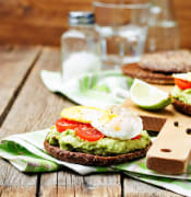 smashed avocado tomatoes egg sandwich on wooden background low