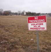 640px No Trespassing sign at empty lot Wikimedia by Rutebega