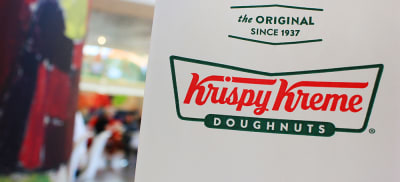 Krispy Kreme doughnuts in to go paper bag on shopping mall blurred background in Moscow on June 2019