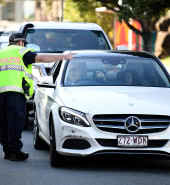 A police officer directs a car for further inspection at a check point on the Queensland-New South Wales border in Coolangatta on the Gold Coast, Wednesday, July 1, 2020. Queensland will open its borders with all the other states and territories apart from from Victoria, on July 10. (AAP Image/Dan Peled) NO ARCHIVING