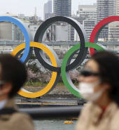 People wearing a mask walk near the Olympics
